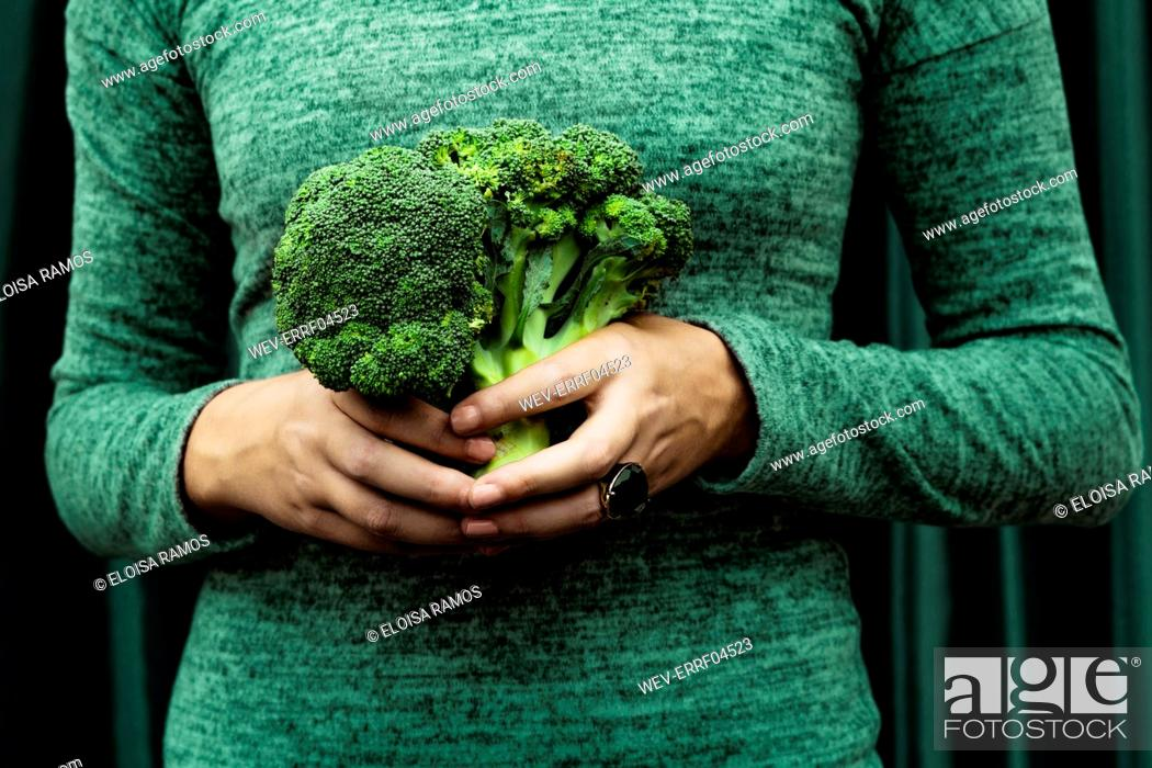 Stock Photo: Midsection of woman standing with broccoli against curtain.