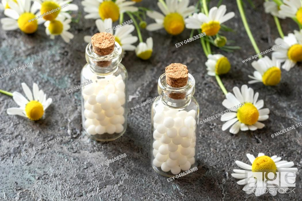 Stock Photo: Bottles of homeopathic remedies with fresh chamomile flowers.