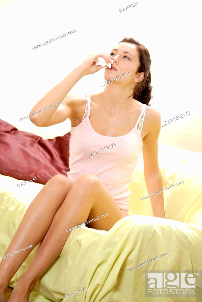 Stock Photo: Woman blowing her nose with a tissue.