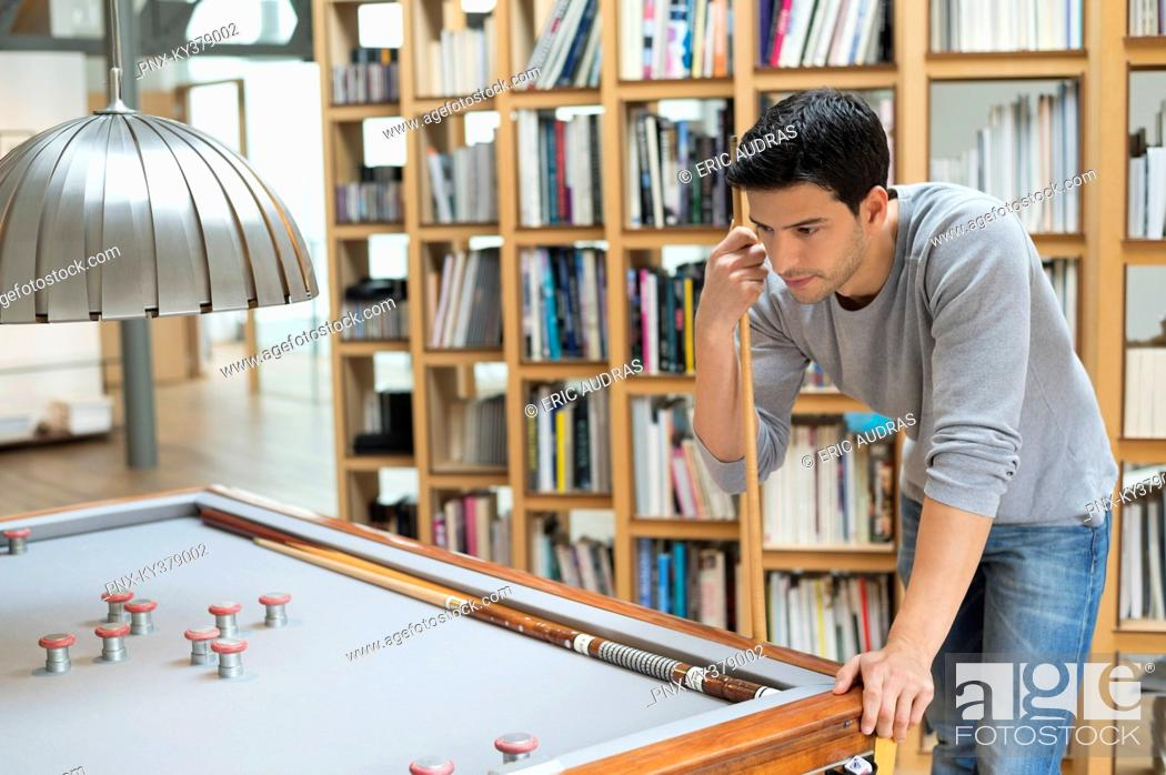Stock Photo: Man looking at a pool table.