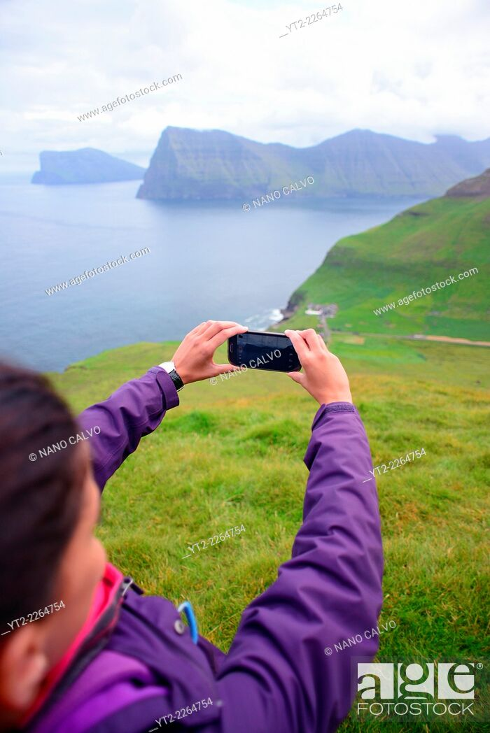 Stock Photo: Young active woman hiking in Kalsoy takes photo with mobile phone, Faroe Islands.