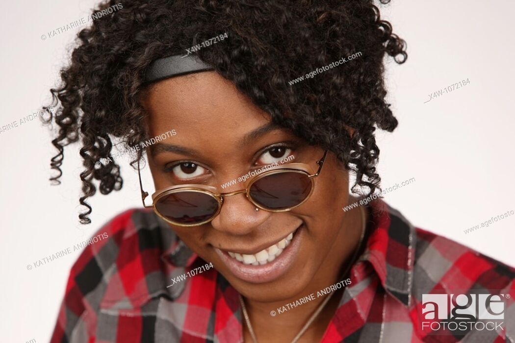 Stock Photo: Young African-American woman looking over sunglasses posing for portrait.