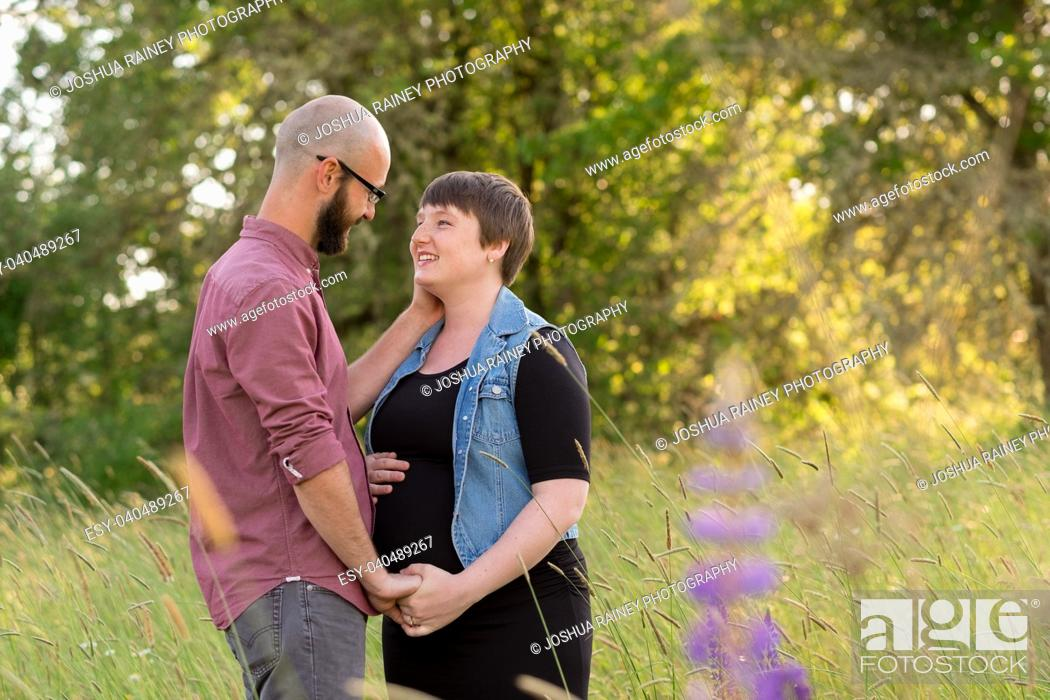 Stock Photo: Man and a pregnant woman in a field in Oregon while the girl is in her third trimester. The couple is married and this husband and wife are expecting their.