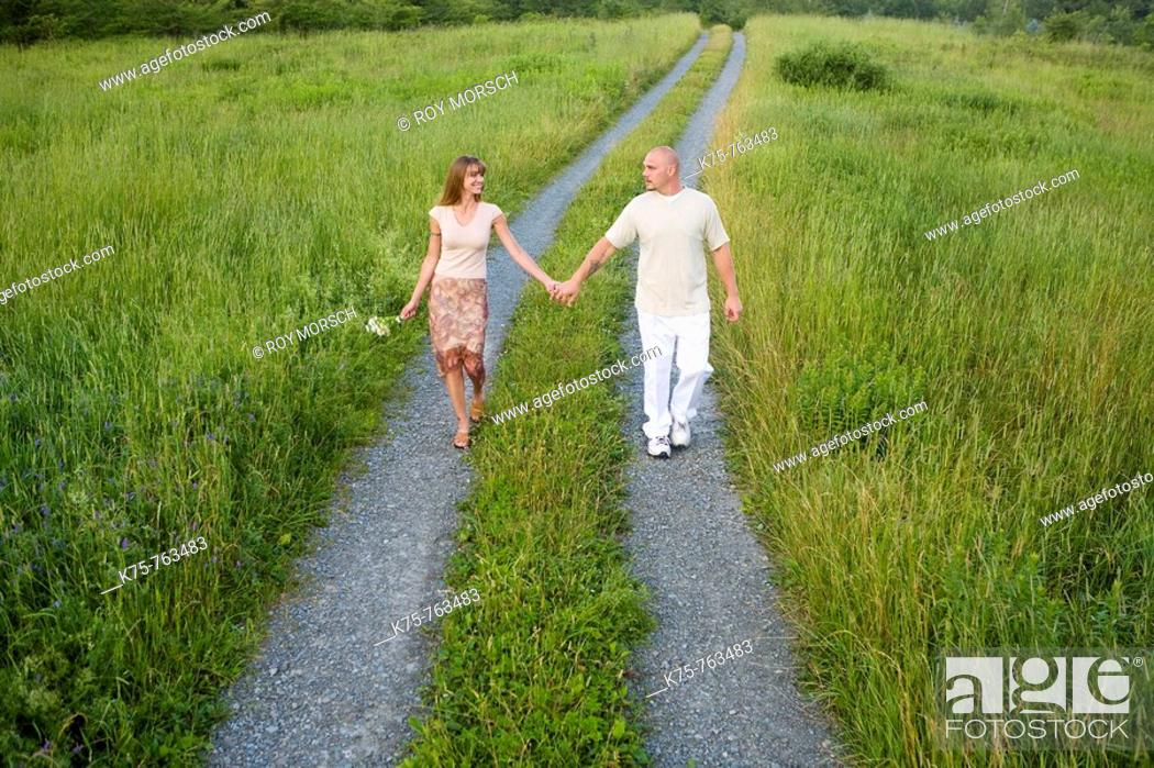 Stock Photo: couple walking down country road holding hands.