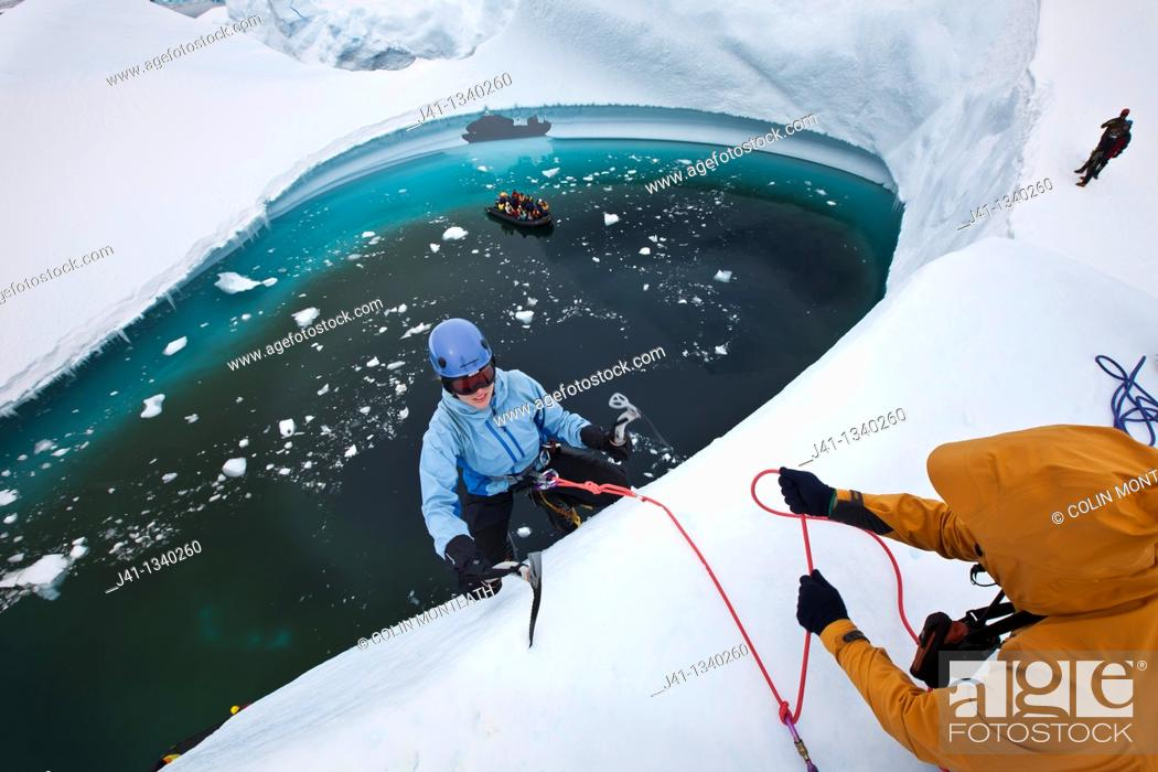 Stock Photo: Guide lowers climbers to base of iceberg , ice climbing on grounded iceberg, Cruise ship passengers look on, Pleneau Island, Antarctic Peninsula.
