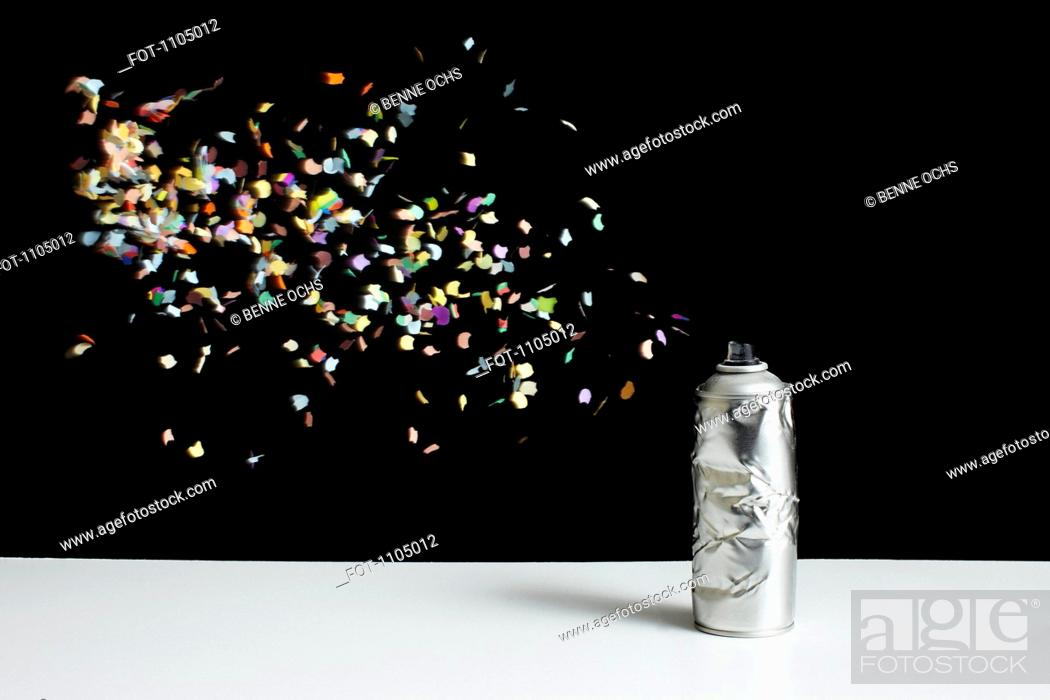 Stock Photo: Floating confetti and a damaged spray paint can.