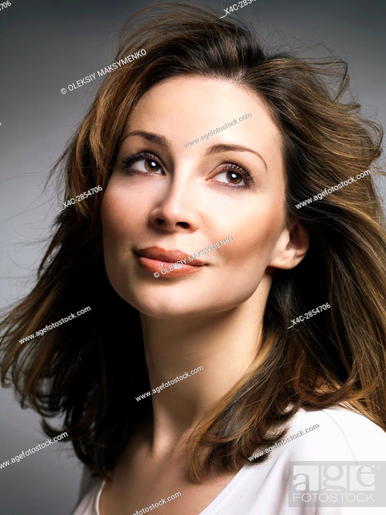 Stock Photo: Portrait of a beautiful smiling caucasian woman with brown hair with daydreaming expression in her thirties.