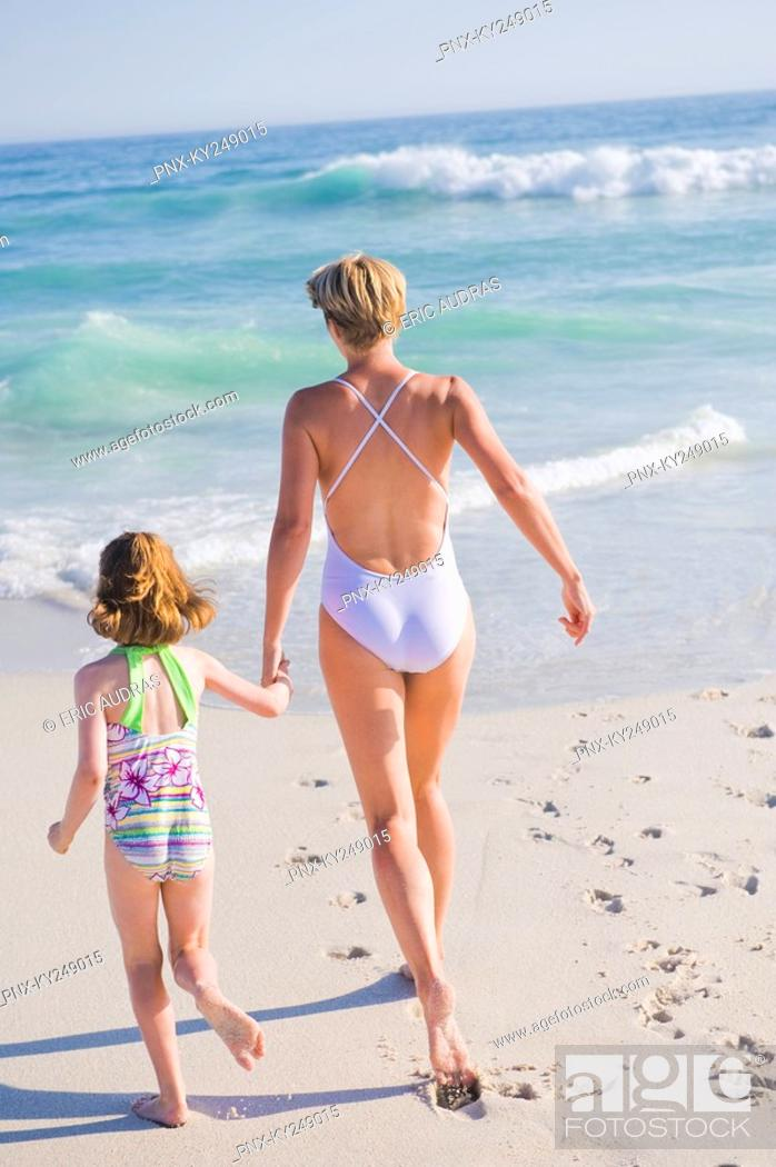Stock Photo: Woman running on the beach with her daughter.