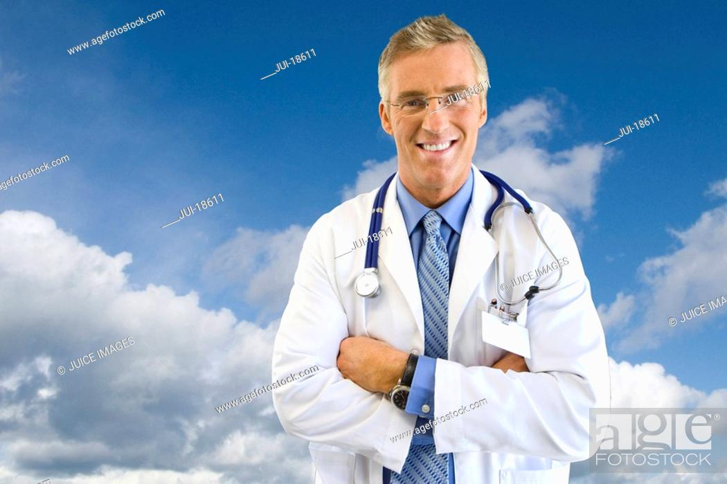 Stock Photo: Portrait of smiling doctor in lab coat with background of clouds in blue sky.