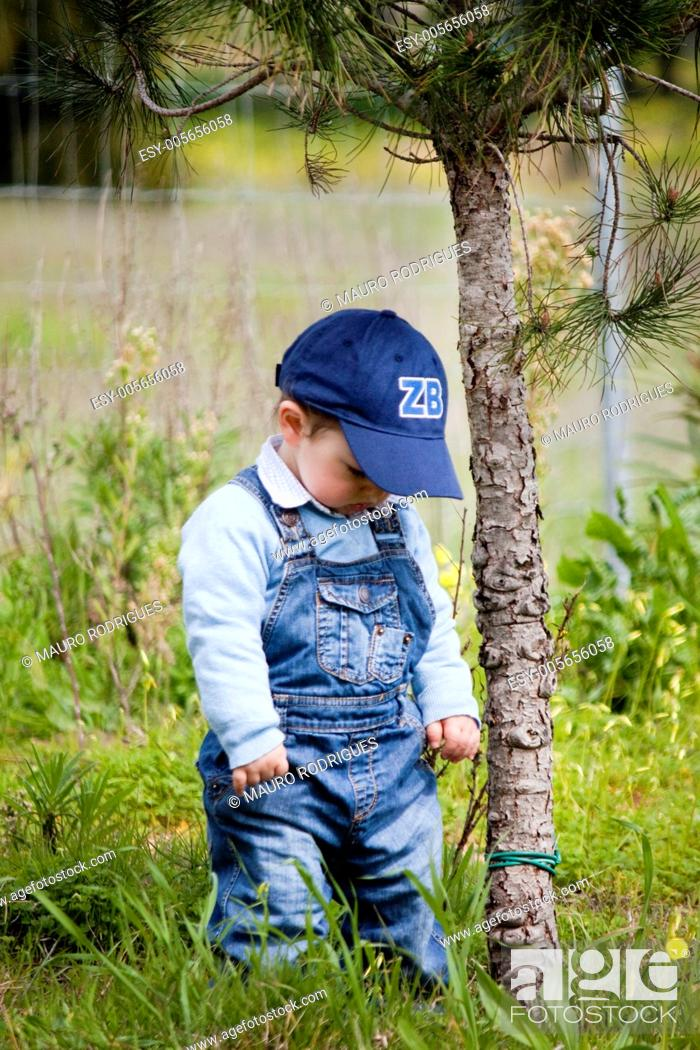 Stock Photo: View of a young child next to a small tree.