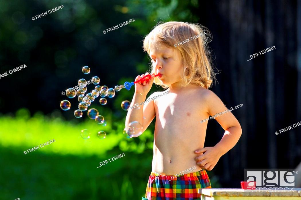 Stock Photo: boy with long blond hair blowing soap bubbles.
