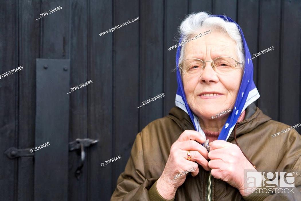 Stock Photo: Frau in ihren Siebzigern bindet sich lachend ein Kopftuch unter dem Kinn zusammen.