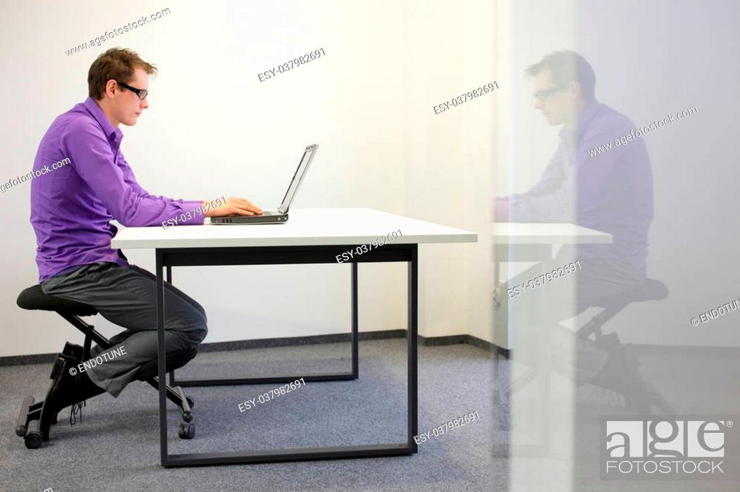 Photo de stock: bad sitting posture at workstation. man on kneeling chair.
