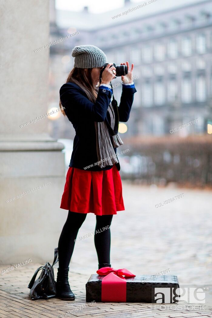 Imagen: Mature woman with Christmas gift taking photographs of city, Copenhagen, Denmark.