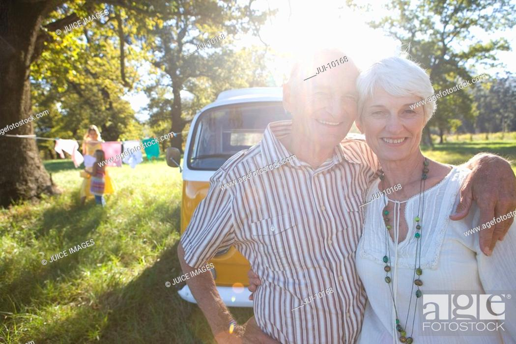 Stock Photo: Senior couple arm in arm by camper van, smiling, portrait lens flare.