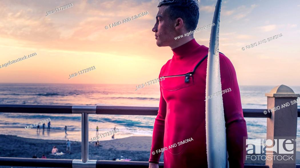 Stock Photo: Young surf athlete look at the ocean waves standing with his surf table outdoor at the beach - surfer active people enjoy nature and healthy lifestyle.