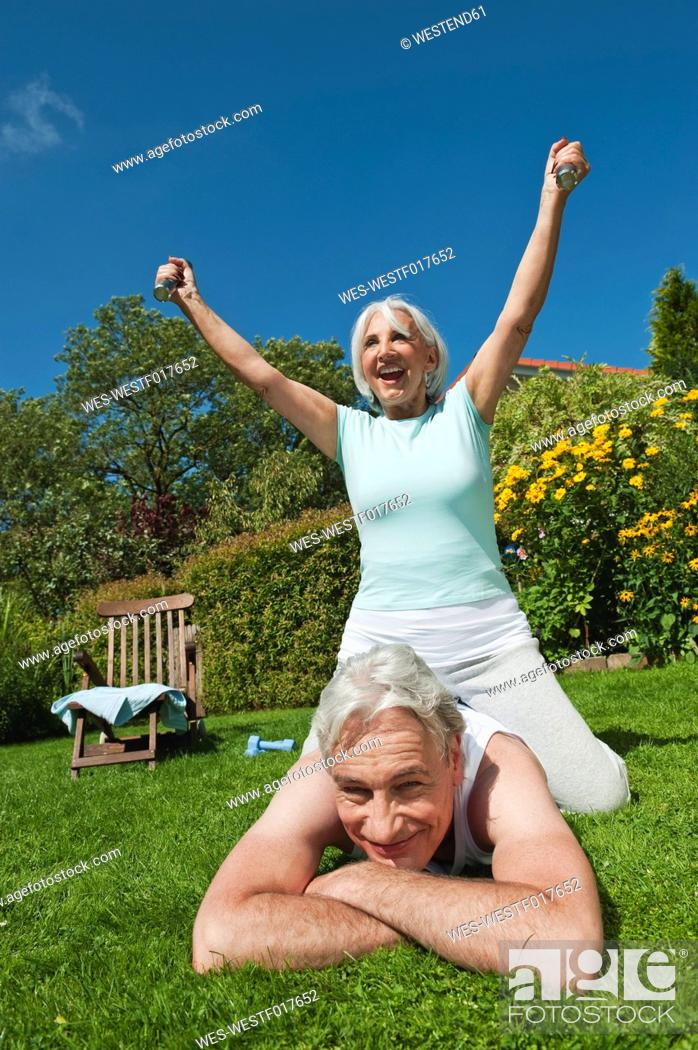 Stock Photo: Germany, Bavaria, Woman sitting on top of man while exercising in garden.