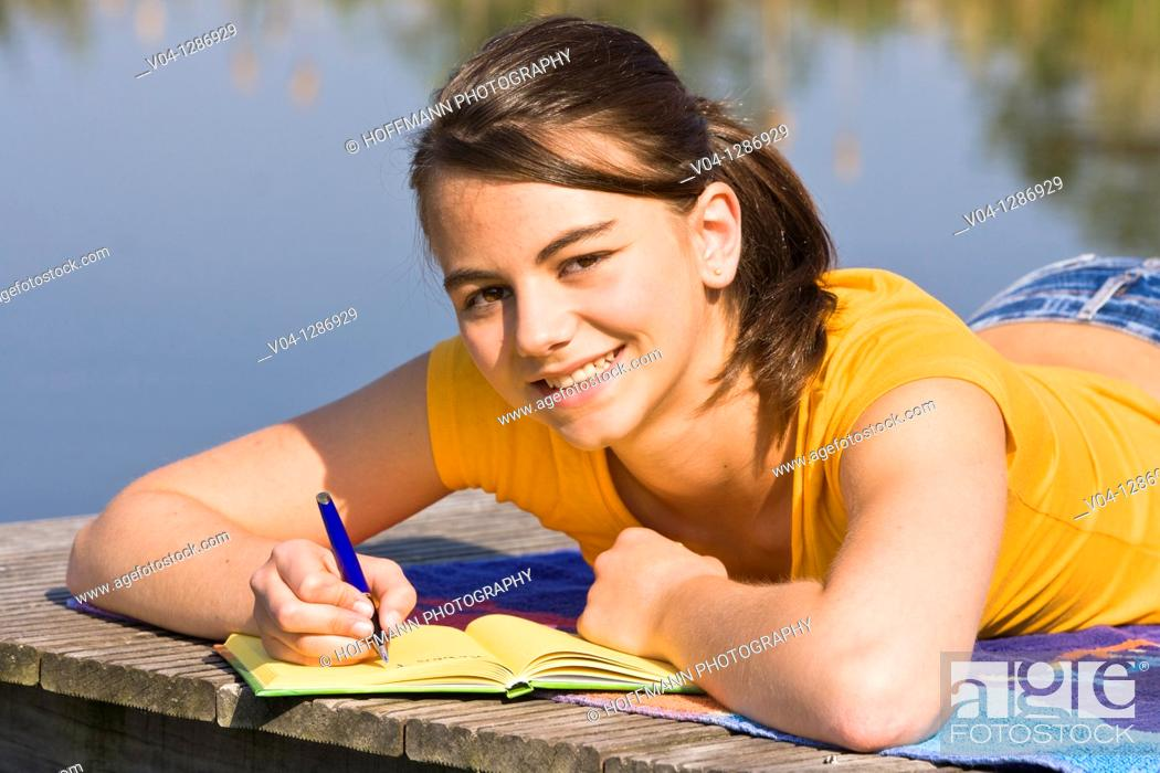 Stock Photo: A young girl writing into her diary at a lake, smiling at the camera.