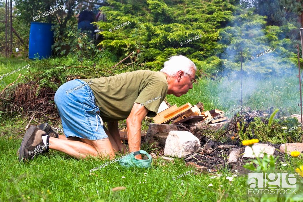 Stock Photo: Senior man trying to make a bonfire in the garden.