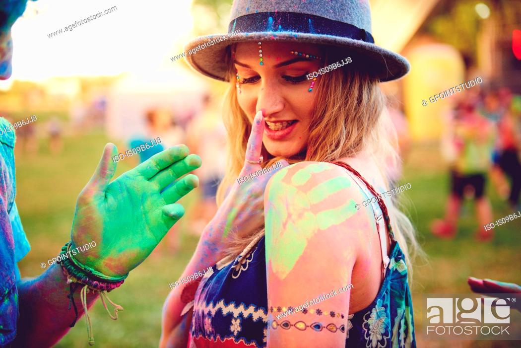 Stock Photo: Young woman with green handprint on shoulder and boyfriend chalked hand at festival.