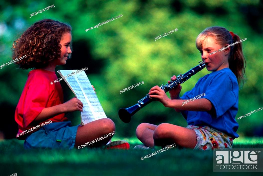 Stock Photo: girl practicing the clarinet with a friend.