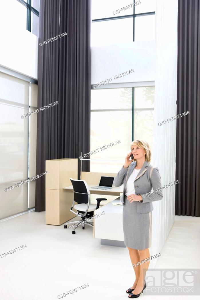Stock Photo: Businesswoman talking on cell phone in office.