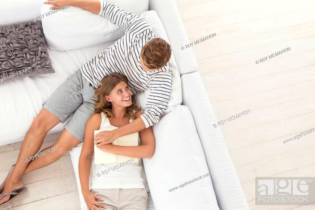 Stock Photo: Smiling woman laying on man's lap on sofa.