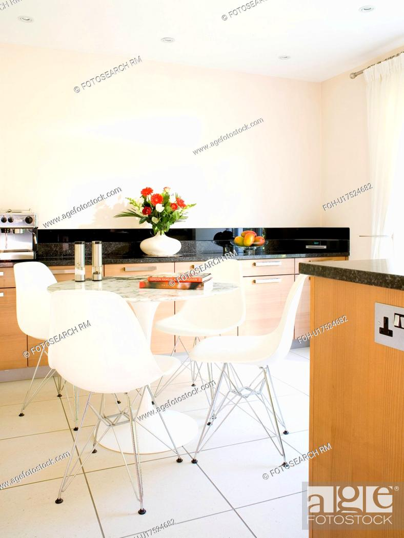 Stock Photo: White Charles Eames DSR dining chairs in modern kitchen dining room with white ceramic tiled floor.