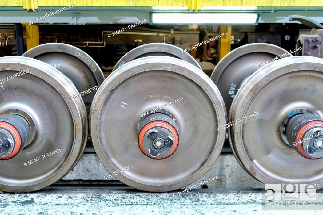 Stock Photo: Locomotive wheel sets in train works, close up.