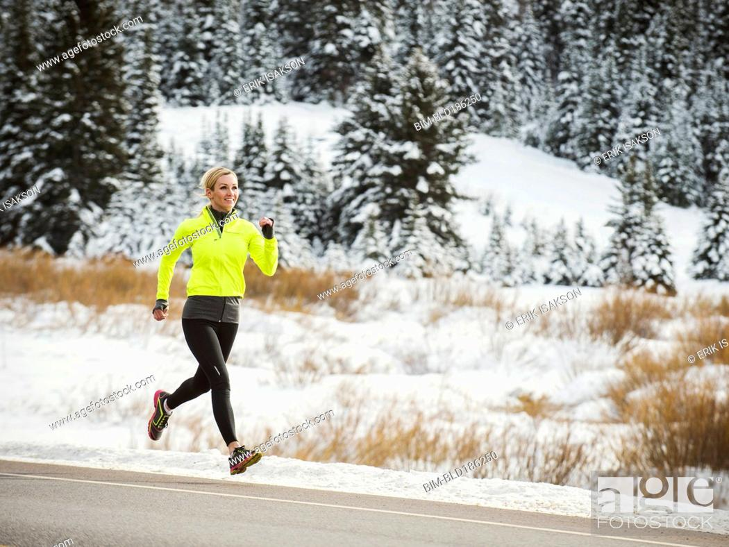 Stock Photo: Caucasian woman running on snowy road.