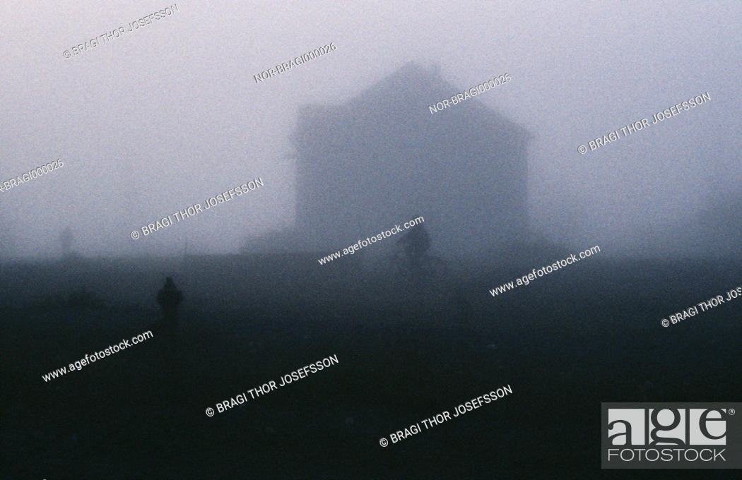 Stock Photo: Silhouette of person on bike in front of house during heavy fog.