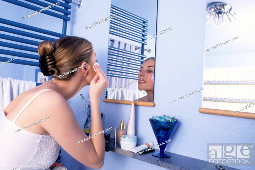 Stock Photo: A young woman, 20-25 25-30 years old, in the bathroom, removing the make-up in front of a mirror.