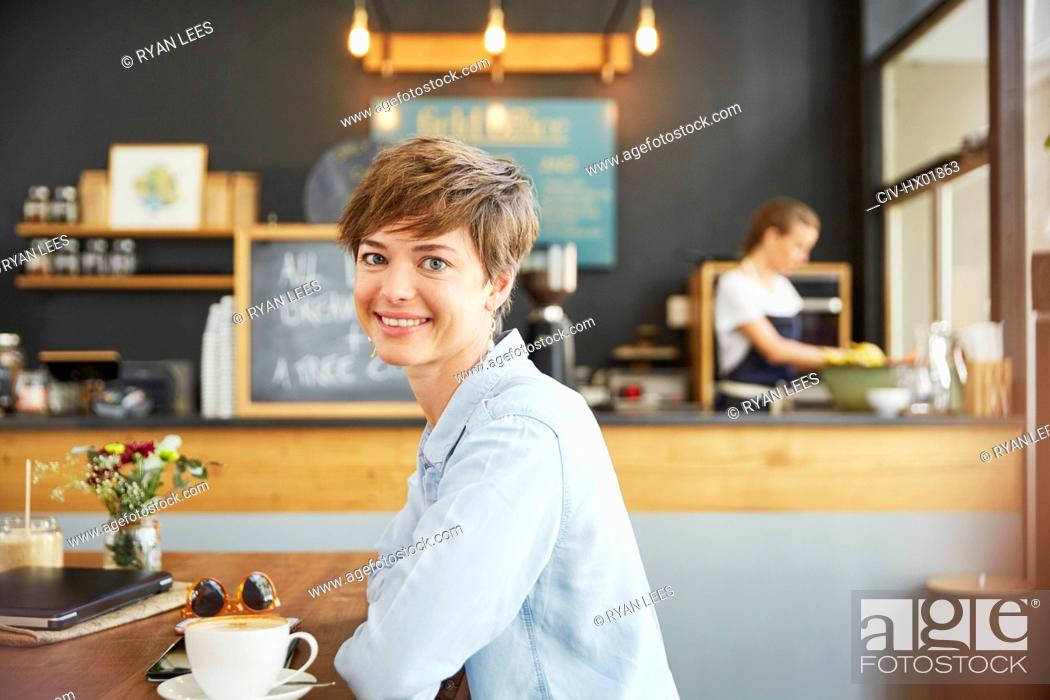 Stock Photo: Portrait smiling woman drinking coffee at cafe table.