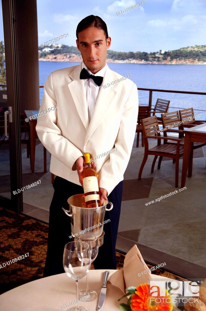 Stock Photo: Waiter displaying wine bottle.