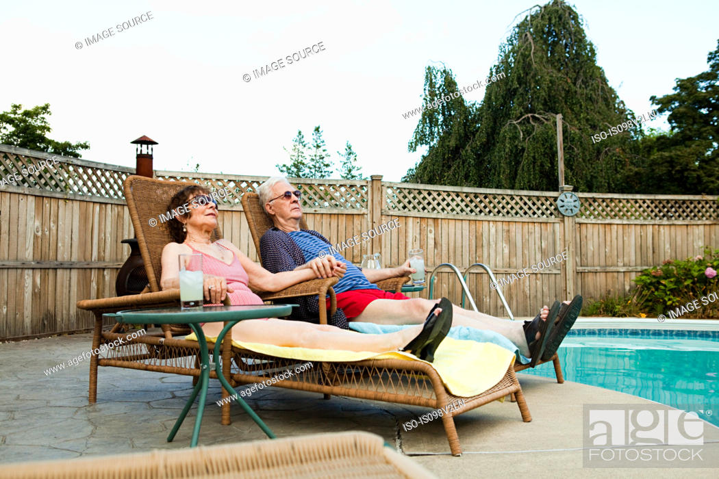 Stock Photo: Senior couple relaxing by swimming pool.