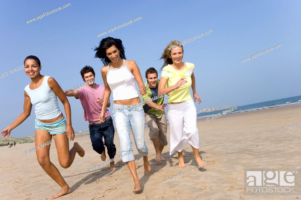 Stock Photo: Young adults running on beach.