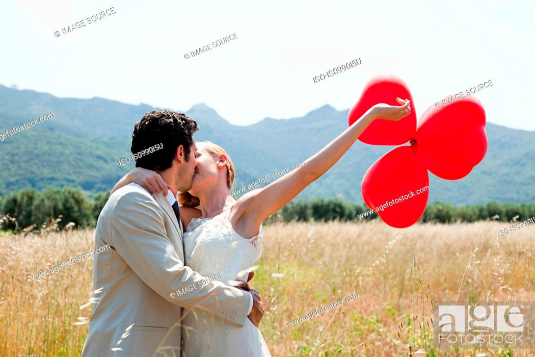 Stock Photo: Newlyweds kissing in field with red heart shape balloons.