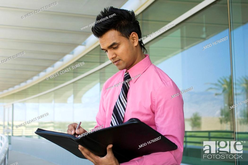 Stock Photo: Businessman Writing in a Planner.