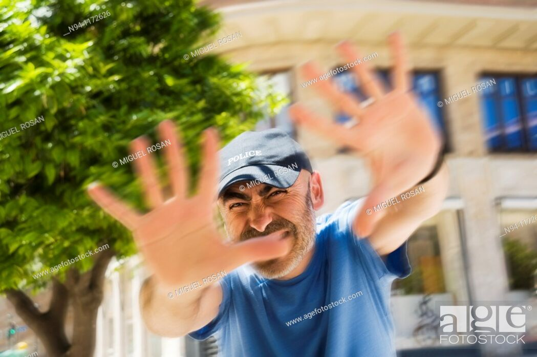Stock Photo: Middle-aged man with a beard and cap, in the center of the city, with open hands scold the photographer.
