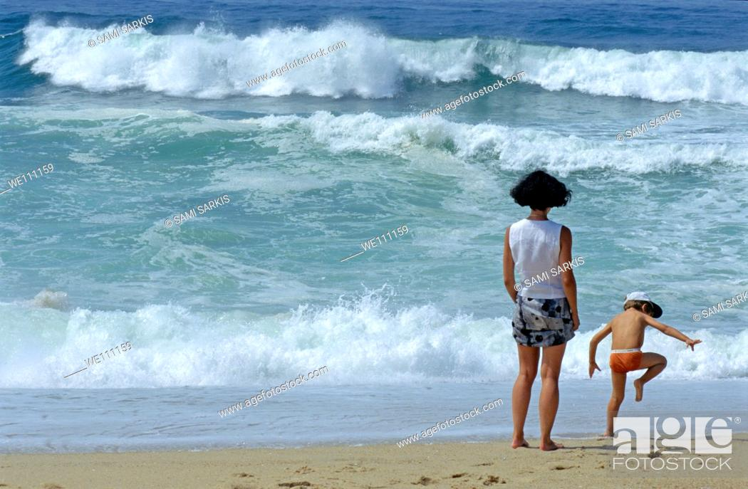 Stock Photo: Mother and children on a beach facing the ocean.