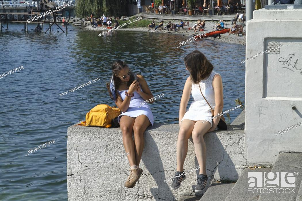 Imagen: tow girls by a lake, taking photo one of the other, smartphone.