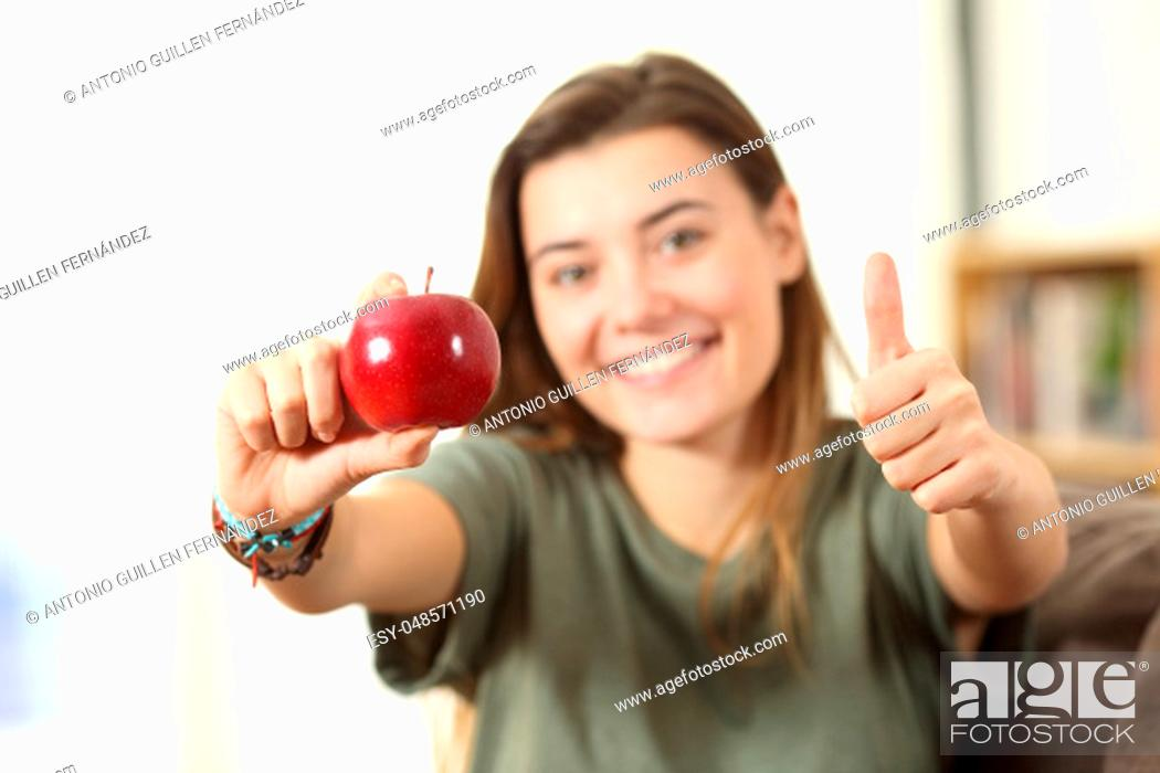 Stock Photo: Front view portrait of a healthy teen showing an apple with thumbs up at home.