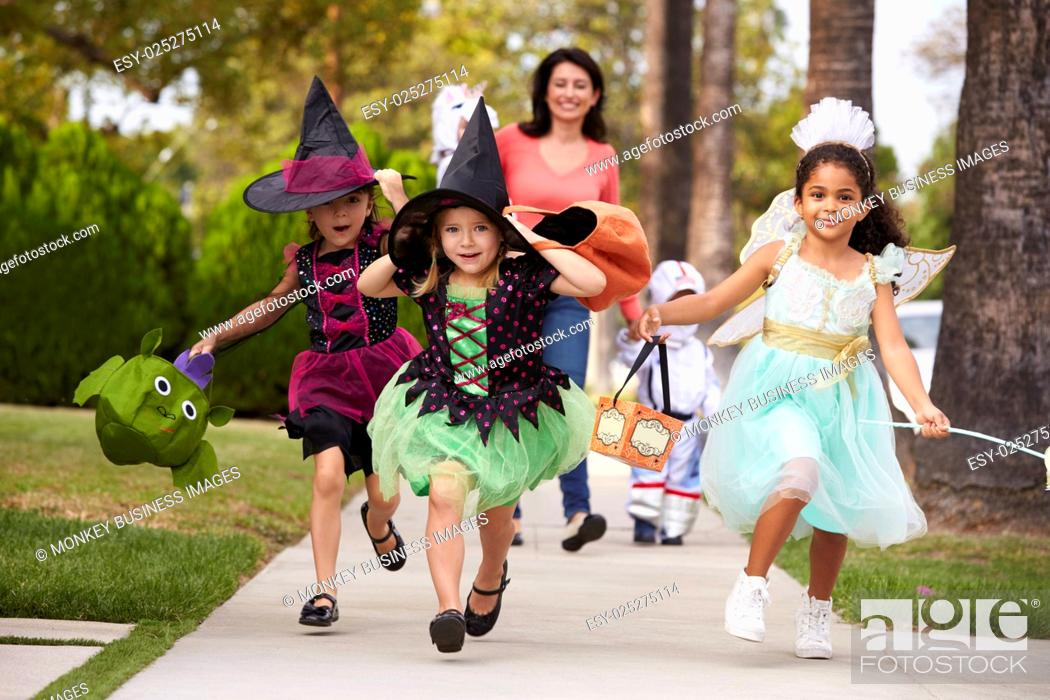Stock Photo: Parent Taking Children Trick Or Treating At Halloween.