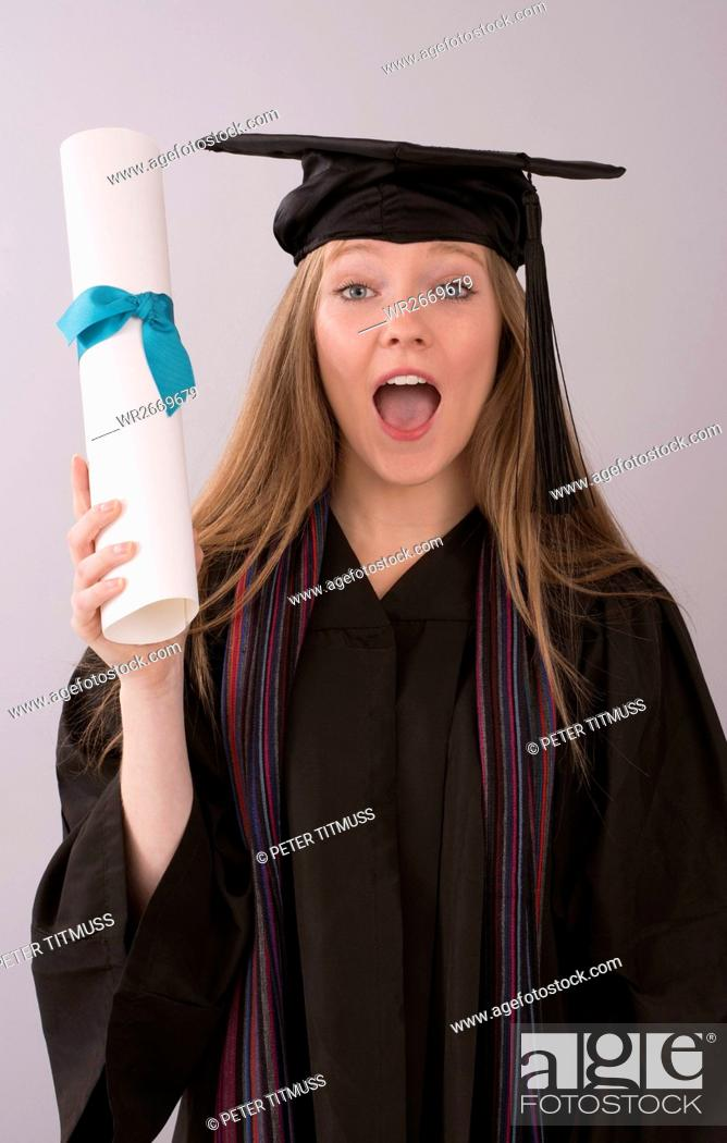 Stock Photo: Young graduate in cap and gown with diploma.