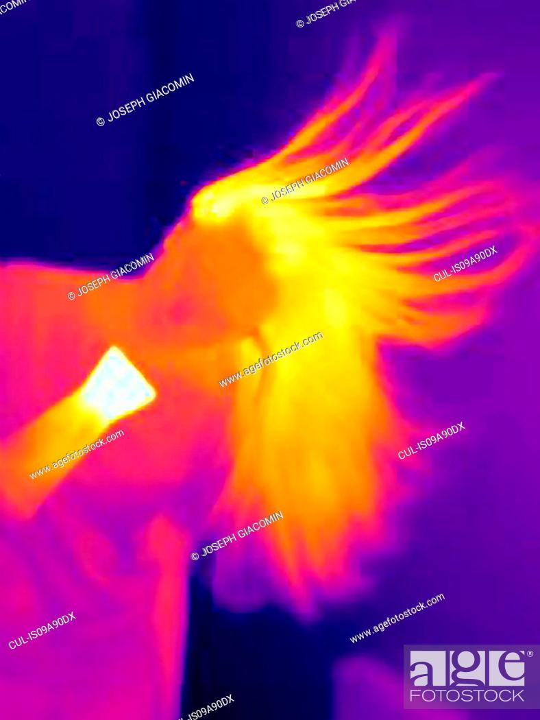 Stock Photo: Thermal image of young woman drying her hair.