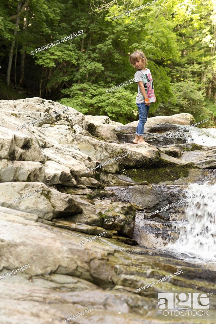 Photo de stock: Girl next to the Waterfall of the bucket in the Selva de Irati in Navarra, Spain.