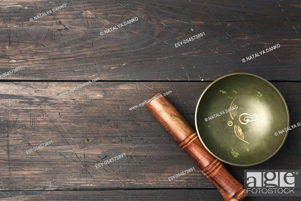 Imagen: Tibetan singing copper bowl with a wooden clapper on a brown wooden table, objects for meditation and alternative medicine, top view, copy space.