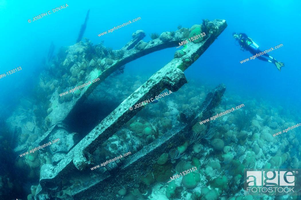Stock Photo: Scuba diver explores rudder post of ship wreck Pollockshields, Bermuda Island, Atlantic.