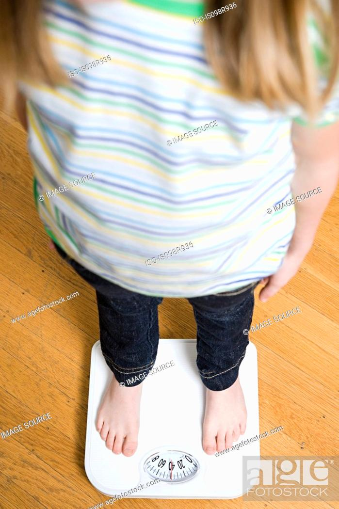 Stock Photo: Girl standing on scales.