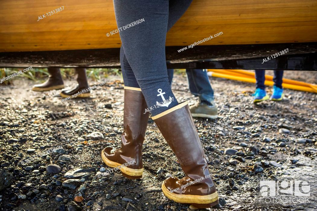 Imagen: Close up of woman walking in rubber boots carrying a wooden boat, South-central Alaska; Homer, Alaska, United States of America.